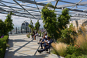 Lunchtime City workers enjoy a tranquill lunchtime high above the City on the rooftop garden at Fen Court in the City of London, the capital's financial district (aka the Square Mile), on 22nd August 2019, in London, England.
