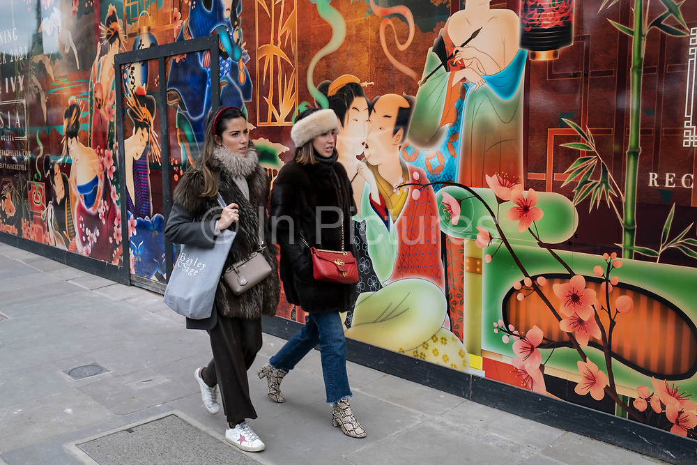 People interacting with a colourful large scale Japanese design illustration on a hoarding outside a shop being refitted on the Kings Road in the upmarket area of Chelsea on 14th April 2021 in London, United Kingdom. Chelsea is one of the principal areas for mid-range, exclusive or luxury goods in West London. It is known as a district where the rich and wealthy shop, mostly for high end ad well as high street fashion and jewellery.