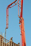 Orange concrete pump with a blue sky background at a construction site