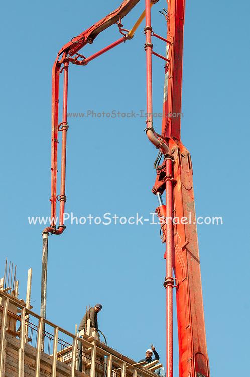 Orange concrete pump with a blue sky background at a construction site