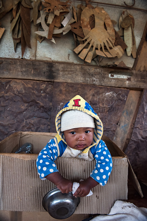 Deaf workers<br /> Metal factory<br /> making metal artefacts for tourist industry<br /> Antananarivo<br /> MADAGASCAR<br /> Baby of worker