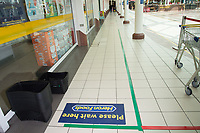 Non-essential shops start open with people queueing outside with social distance 2 metre rules. High streets up here seem slower than expected. Inside the shopping centre is all marked out for walking and queuing. Liscard near Liverpool.