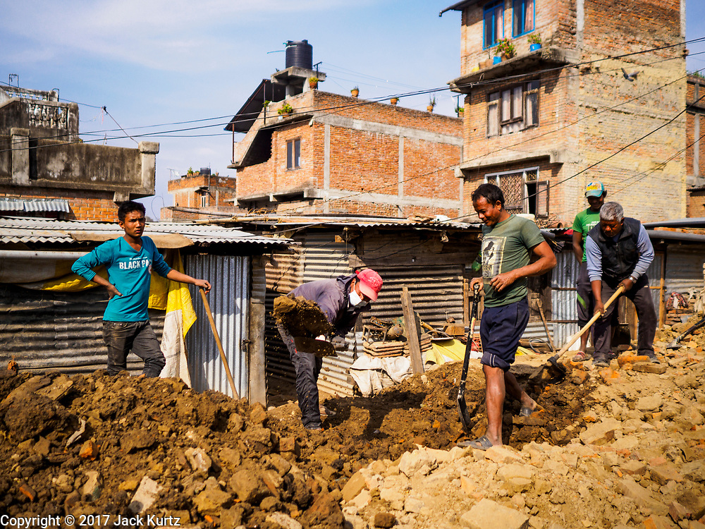 15 MARCH 2017 - BUNGAMATI, NEPAL: Workers dig out the ruins of an ancient Hindu temple in Bungamati. The temple was destroyed in the 2015 Nepal earthquake. Bungamati, a community of wood carvers and artisans, used to be a stop on the tourist trail of the Kathmandu valley but since the 2015 earthquake few tourists visit the community. Recovery seems to have barely begun nearly two years after the earthquake of 25 April 2015 that devastated Nepal. In some villages in the Kathmandu valley workers are working by hand to remove ruble and dig out destroyed buildings. About 9,000 people were killed and another 22,000 injured by the earthquake. The epicenter of the earthquake was east of the Gorka district.            PHOTO BY JACK KURTZ