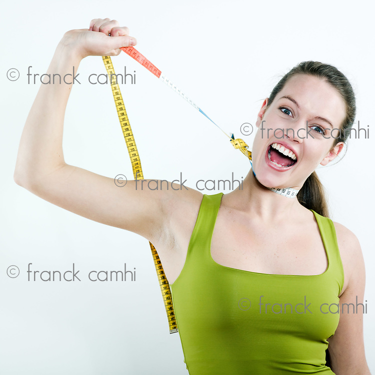 studio portrait on isolated background of a young beautiful caucasian woman strangle by a meter ribbon