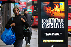 © Licensed to London News Pictures. 20/01/2021. London, UK. A woman walks past the government's 'Bending The Rules Costs Lives' publicity campaign poster in north London, after the mutated variant of the SARS-Cov-2 virus continues to spread around the country. On Tuesday 19 January, 1,610 people died in the UK within 28 days of a positive Covid-19 test. This is the biggest figure reported in a single day in the UK since the pandemic began last year. According to government figures over 4.2 million people have now received the first dose of a vaccine. Photo credit: Dinendra Haria/LNP