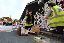 © Licensed to London News Pictures. 23/07/2021. Manchester, UK.  University of Manchester students carefully remove messages left at the mural of Marcus Rashford in Manchester. The messages are to be taken away for preservation, amid worries that they will disintegrate in the rain. Photo credit: Adam Vaughan/LNP