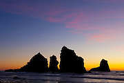 The Motukiekie Rocks are a cluster of spectacular sea stacks located on the New Zealand coast near Greigs. They are rendered in silhouette after sunset.