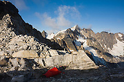 Jim Prager enjoys the views of Mount Fury and the Northern Picket Range, standing on a boulder above camp at Luna Col, North Cascades National Park, Washington.