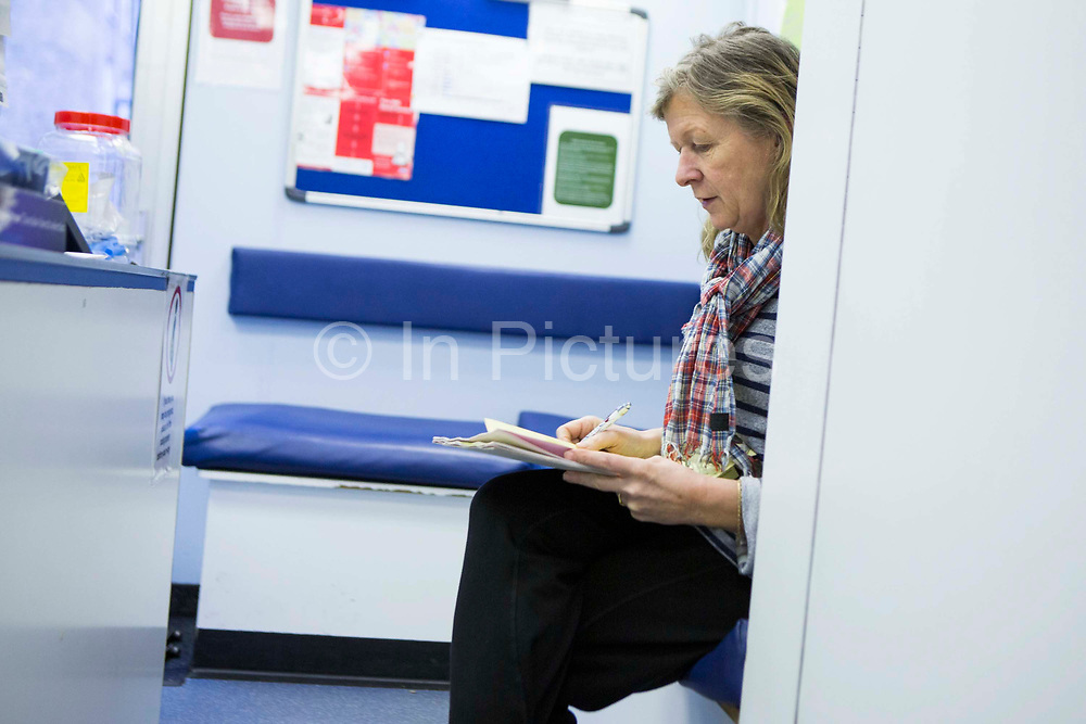 Diana, a female radiographer, sits and reviews a patient't medical notes on the Mobile X-ray Unit (MXU).  The MXU van is parked outside a hostel in central London and the visit is part of a public health intervention for Active Case Finding for TB in hard to reach groups.  The rates of TB in London are higher than any other Western European capital and is a major public health problem. TB is an infectious disease, but treatable and curable if diagnosed in time. Early diagnosis is a key to TB control and Active Case Finding is an important part of this.