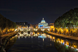 Illuminated St. Peter's Basilica by bridge over river at night, Rome, Italy