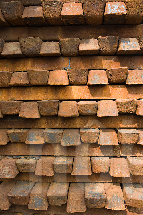 Color film photograph of a stack of iron blocks in Da Hoi steel production craft village, Hanoi outskirts, Vietnam, Southeast Asia