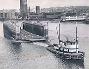 A 1,000-ton wooden floating drydock, purchased by the Lake Union Drydock Company as surplus equipment from the United States Maritime Commission, was shown from the Ballard Bridge as it arrived in Seattle after being towed from Scow Bay, near Port Townsend, by the tugboat Sandra Foss. The drydock was 240 feet long and 64 feet wide. (Roy Scully / The Seattle Times, 1947)