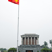 A Vietnamese flag flies in front of the Ho Chi Minh Mausoleum as tourists wander in the square in front. A large memorial in downtown Hanoi surrounded by Ba Dinh Square, the Ho Chi Minh Mausoleum houses the embalmed body of former Vietnamese leader and founding president Ho Chi Minh.
