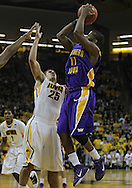 December 07 2010: Northern Iowa Panthers guard Kwadzo Ahelegbe (11) puts up a shot over Iowa Hawkeyes guard Eric May (25) during the first half of their NCAA basketball game at Carver-Hawkeye Arena in Iowa City, Iowa on December 7, 2010. Iowa defeated Northern Iowa 51-39.