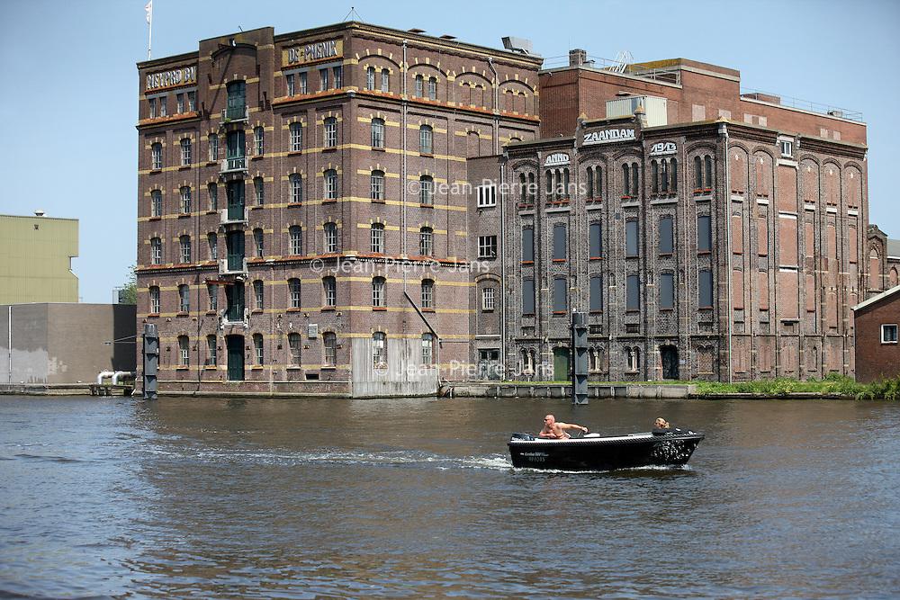 Nederland, Zaandam , 5 juli 2013.<br /> Wandeling door de binnenstad van Zaandam.<br /> Starten bij De Werf aan de Oostzijde. Daarvandaan kun je lopen op een soort boulevard tussen de flats en het water. De eerste stop is De Fabriek, filmhuis en eetcafé met terras aan de Zaan met uitzicht op de sluis. Daarna de sluis zelf.<br /> Dan langs het winkelgebied richting de Koekfabriek: Het oude Verkade pand dat is verbouwd en waar nu de bieb en sportschool en restaurant etc. in zitten.<br /> (Dat is aan de overkant van het startpunt) en misschien nog de Zwaardemaker meepakken aan de Oostzijde. Dat is een oud pakhuis die Rochdale enige jaren geleden heeft verbouwt tot appartementen met een stukje Nieuwbouw.<br /> Ook doen: het Russische buurtje vlakbij de Zaan. Dit jaar staat Rusland in de schijnwerpers en Zaandam heeft een speciale band met Rusland, vanwege het Czaar Peterhuisje en de Russische buurt. <br /> Op de foto: Bootje varen over de Zaan. Op de achtrgrond een oude pakhuis de Phenix<br /> Foto:Jean-Pierre Jans