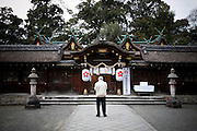 KYOTO, JAPAN, HiranoJinja  - a Man pray in front of the shrine - March 2011