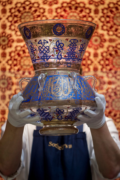 """© Licensed to London News Pictures. 29/03/2021. LONDON, UK. A staff member presents """"a large mamluk revival enamelled glass mosque lamp"""", 20thC (est. £8,000-12000). Preview of the upcoming Arts of the Islamic World & India sale where historic objects, paintings and manuscripts from the last 1,000 years are to be auctioned on 31 March at Sotheby's New Bond Street galleries.  Photo credit: Stephen Chung/LNP"""