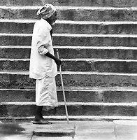 Sri Lankan man with a walking stick approaches a set of stairs in a temple.