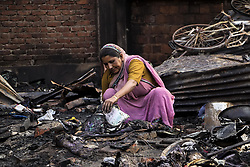 May 3, 2017 - Guwahati, Assam, India - A woman pulling out half burnt text books of her children from the burnt remains of her house at Ambari, Guwahati on May 03, 2017. A major fire broke out in Ambari area of Guwahati yesterday night, destroying around 30 shanties rendering as many families homeless. In Guwahati, on 03-05-17. (Credit Image: © Vikramjit Kakati via ZUMA Wire)