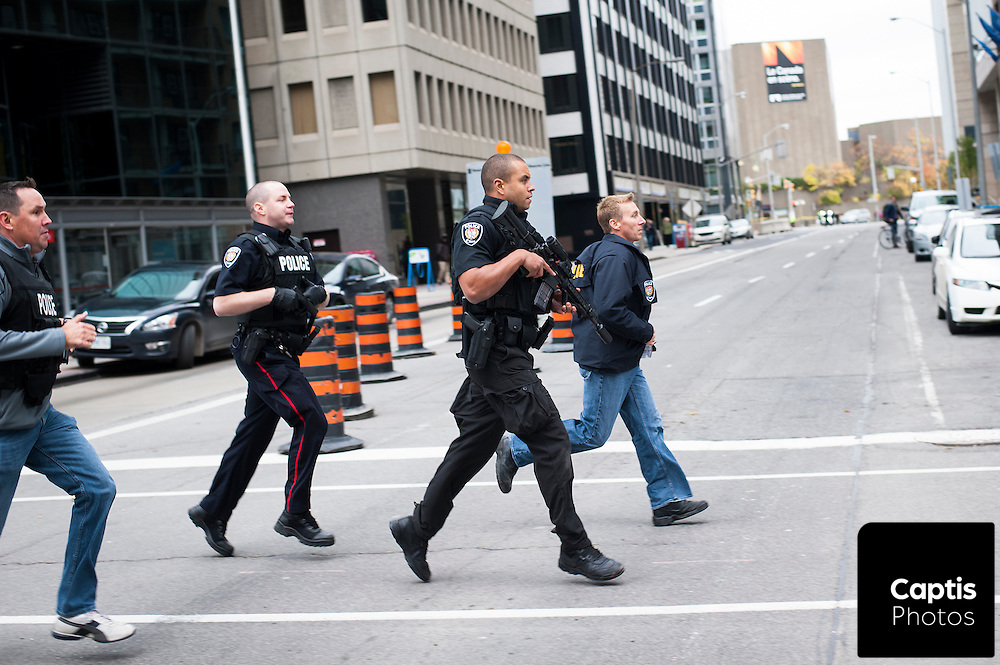 Police run down Metcalfe street to securing a building in Ottawa's downtown core following the shooting of Cpl. Nathan Cirillo. October 22, 2014.