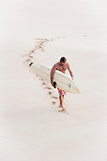 A surfer walks out of the water at Waimea Bay on Oahu, North Shore.