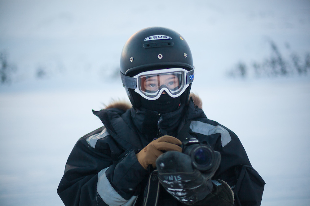 UNIS student Kiya Riverman takes pictures in the cold in Adventdalen, Svalbard on a class field trip by snowmobile to Rabotbreen.