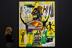 """© Licensed to London News Pictures. 27/09/2019. LONDON, UK.  A staff member views """"Pyro"""", 1984, by Jean-Michel Basquiat (Est. above GBP 9m).  Preview of Sotheby's Frieze Week Contemporary Art exhibition at its New Bond Street galleries.  Over 250 works by artists, including Andy Warhol, David Hockney and Jean-Michel Basquiat, will be auctioned on 3 October 2019.  Photo credit: Stephen Chung/LNP"""