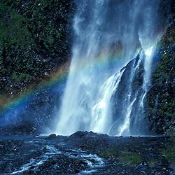 Bridal Veil Falls, Thompson Pass, AK.   A rainbow decorates this beautiful waterfall. Near Valdez, AK.