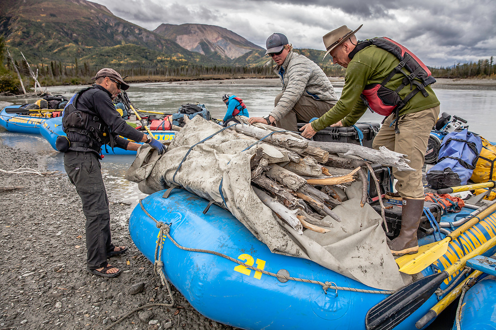 River guides Alan Christie, Brad Goodwin and Neil Hartling secure fire wood to the rafts in the Tatshenshini-Alsek Provincial Park in British Columbia, Canada on September 2, 2016.