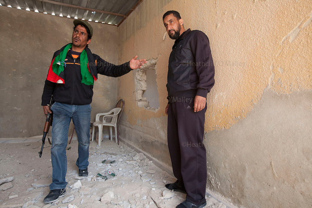 Mcc0030300 . Sunday Telegraph..Zacharia Mufta points to where a dud tank shell landed in his home in the town of Ajdabiyah after Libyan government forces retreated on saturday night due to repeated attacks from NATO airstrikes...Ajdabiyah 26 March 2011