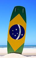 "brazilian flag painted on a kite surf board with ""praia e vento"" (beach and wind) instead of ""ordem e progresso""  in prainha beach near fortaleza"