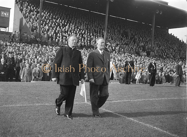 GAA official and priest walking out onto the pitch before the beginning of the Kerry v Meath All Ireland Senior Gaelic Football Final, 26th September 1954. Meath 1-13 Kerry 1-7.
