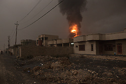Licensed to London News Pictures. 08/11/2016. Qayyarah, Iraq. A burning oil valve is seen beyond soot blackened houses, which are currently inhabited, under a smoke filled sky in the town of Qayyarah, Iraq. Oil wells in and around the town of Qayyarah, Iraq, we set alight in July 2016 by Islamic State extremists as the Iraqi military began an offensive to liberated the town.<br /> <br /> For two months the residents of the town have lived under an almost constant smoke cloud, the only respite coming when the wind changes. Those in the town, despite having been freed from ISIS occupation, now live with little power, a water supply tainted with oil that only comes on periodically and an oppressive cloud of smoke that coats everything with thick soot. Many complain of respiratory problems, but the long term health implications for the men, women and children living in the town have yet to be seen. Photo credit: Matt Cetti-Roberts/LNP