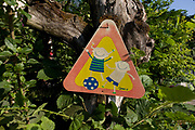 A children playing warning sign in a rural location in northern Italy. The cartoon qualities of the children smiling while playing with their ball is on the side of a quiet road in the lower Dolomites. The quiet hamlet of Steinegger is a dead end but kids are encouraged to run around in their peaceful corner of Italy, well away from heavy traffic and surrounded by vineyards.