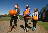 Mackenzie Rois, Anna Cook and Brenna O'Connor carry three of the approximately 350 pumpkins that were donated for Gilford Middle Students to carve on Thursday afternoon for the upcoming Pumpkin Festival in Laconia this weekend.  (Karen Bobotas/for the Laconia Daily Sun)