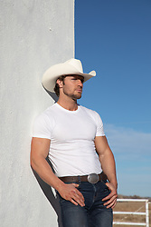 All American cowboy leaning against a white wall on a ranch