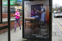 © Licensed to London News Pictures. 20/03/2021. London, UK. A joggers runs past the 'It's about our healthcare' the Office for National Statistics (ONS) Census Day 2021 poster in north London. The Census Day is on 21 March 2021. Every household located in England, Wales and Northern Ireland is legally obligated to fill out the survey or could be fined up to £1,000. The ONS is planning on publishing the initial findings from the Census in March 2022, followed by the full results covering all Census data in March 2023. Photo credit: Dinendra Haria/LNP