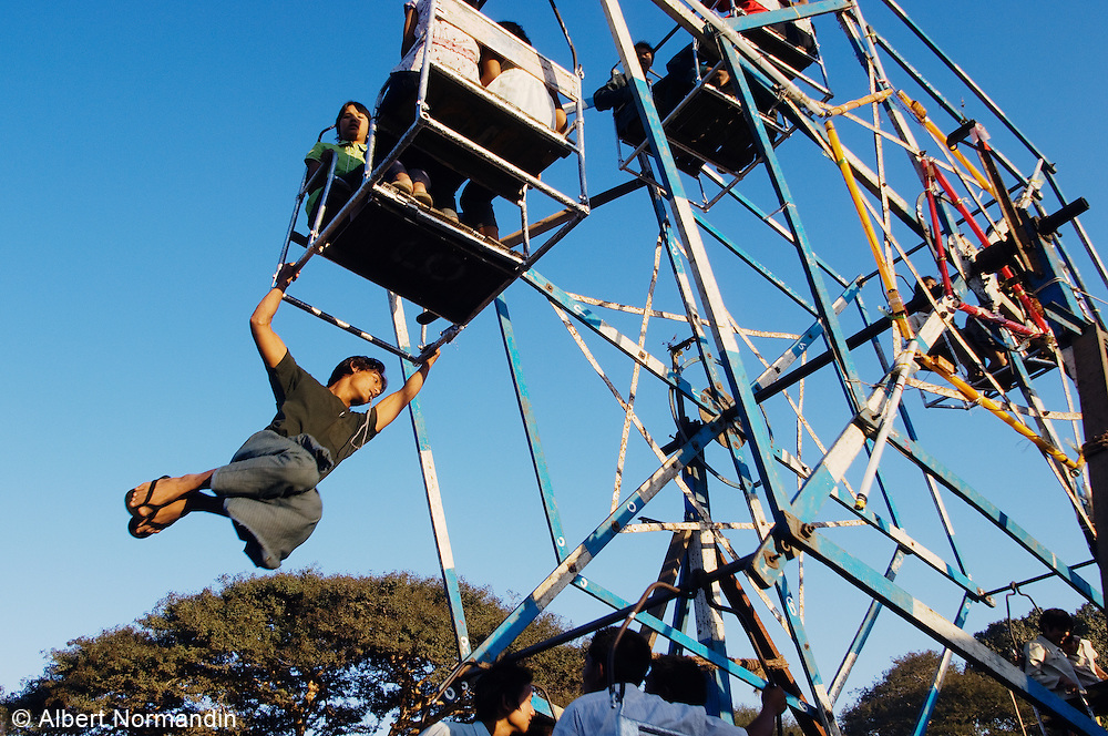 Young man swinging on ferris wheel as power supply