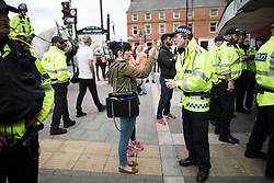© Licensed to London News Pictures . 29/07/2017 . Rochdale , UK . A woman video records a police inspector during a confrontation as police detain Asian youths to Prevent a Breach of the Peace , and hand out dispersal notices , after an anti-fascist counter demonstration in the town . Far-right street protest movement , the English Defence League ( EDL ) , hold a demonstration in Rochdale , opposed by anti-fascists , including Unite Against Fascism ( UAF ) . The EDL say they are demonstrating against the sexual grooming and abuse of English girls by Muslim men in Rochdale and against terrorism across the UK . Photo credit : Joel Goodman/LNP