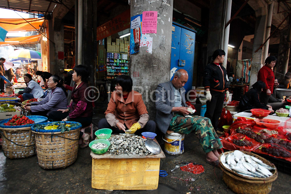 Vegetable and fish sellers wait for customers in the old city quarter in Xiamen, Fujian Province, China, on Thursday, March 05, 2009.  Once a famous treaty port, Xiamen is now know for it's colonial architecture and laid back way of life.