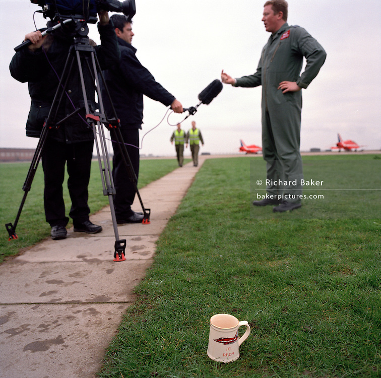 Pilot of the Red Arrows, Britain's RAF aerobatic team answers questions to local tv station, having left his cup of tea.