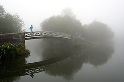 © Licensed to London News Pictures. 15/09/2016. Birmingham, West Midlands,  UK. A jogger crosses a bridge on the Birmingham canal system. Heavy fog envelopes Birmingham in the early  morning ahead of a day of temperatures forecast to reach 25 deg centigade in Birmingham, West Midlands, UK. Photo credit: Graham M. Lawrence/LNP