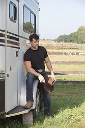 good looking cowboy sitting on a horse trailer