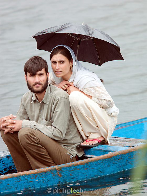 Locals shelter from rain on a shikara, a local wooden boat, on Lake Dal, Srinigar, Kashmir, India