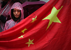 © Licensed to London News Pictures. 21/10/2015. London, UK. A supporter of Chinese President Xi Jinping waits in the rain opposite Downing Street. Photo credit: Peter Macdiarmid/LNP