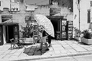 A visitor holdings a big umbrella walks through the streets of Sassi di Matera on July 24, 2020. Sassi di Matera are two districts (Sasso Caveoso and Sasso Barisano) of the Italian city of Matera, Basilicata, well-known for their ancient cave dwellings inhabited since the Paleolithic period.