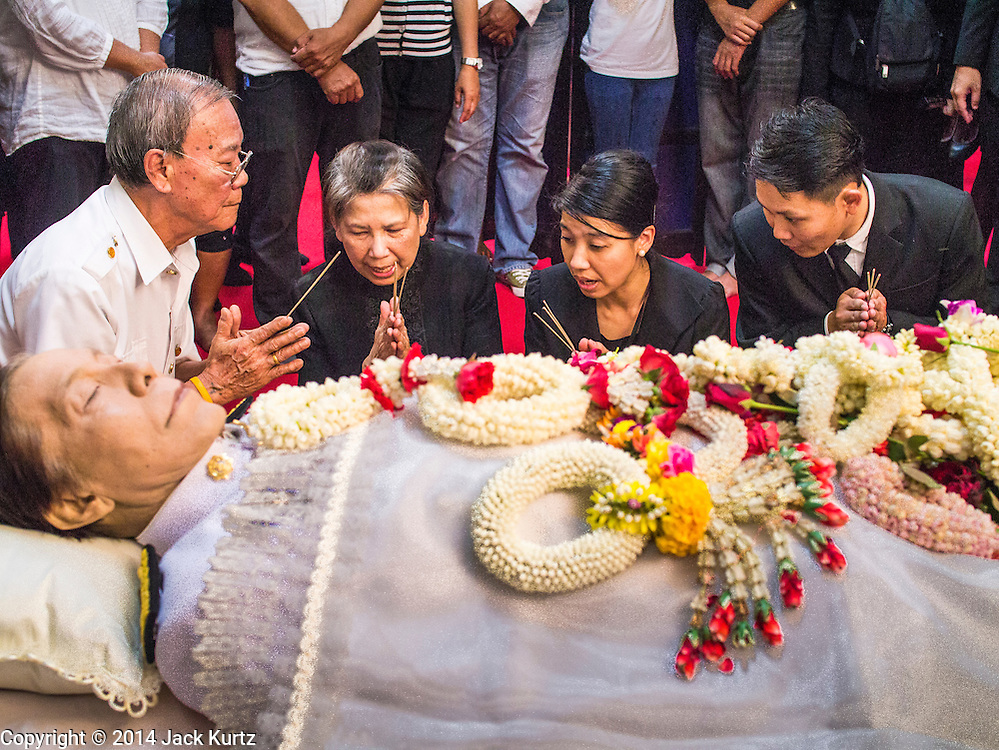 12 OCTOBER 2104 - BANG BUA THONG, NONTHABURI, THAILAND: RATCHANEE WIRIYACHAI, (2nd from left) widow of Apiwan Wiriyachai, and other family members pray next to the body of Apiwan Wiriyachai on the first day of Apiwan's funeral rites at Wat Bang Phai in Bang Bua Thong, a Bangkok suburb, Sunday. Apiwan was a prominent Red Shirt leader, member of the Pheu Thai Party of former Prime Minister Yingluck Shinawatra, and a member of the Thai parliament. The military government that deposed the elected government in May, 2014, charged Apiwan with Lese Majeste for allegedly insulting the Thai Monarchy. Rather than face the charges, Apiwan fled Thailand to the Philippines. He died of a lung infection in the Philippines on Oct. 6. The military government gave his family permission to bring him back to Thailand for the funeral. He will be cremated later in October. The first day of the funeral rites Sunday drew tens of thousands of Red Shirts and their supporters, in the first Red Shirt gathering since the coup.    PHOTO BY JACK KURTZ