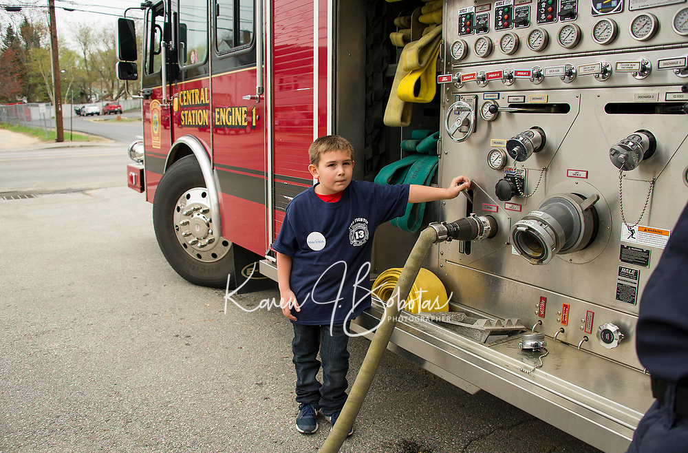 """Paul Swenson fills the water tank up on Engine 1 after putting out out a house fire during his """"Day as a Fireman"""" wish through the Make A Wish Foundation on Sunday at the Laconia Fire Department.  (Karen Bobotas/for the Laconia Daily Sun)"""