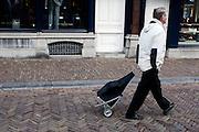 Een man loopt met een boodschappenkarretje door Utrecht.<br /> <br /> A man is walking with his trolley in Utrecht.