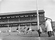 Kerry Goalie J Culloty gathers the ball safely despite the efforts of Galway J Young S Keeley during the All Ireland Senior Gaelic Football Championship Final, Kerry vs Galway in Croke Park on the 27th September 1959. Kerry 3-7 Galway 1-4.